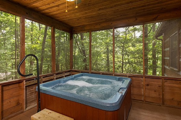 Hot tub on a screened in, covered porch at Little Bear, a 1 bedroom cabin rental located in Pigeon Forge