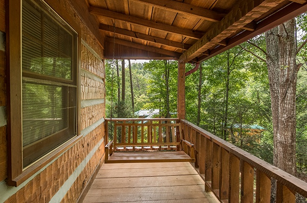 Porch swing on the covered deck surrounded by woods at Little Bear, a 1 bedroom cabin rental located in Pigeon Forge