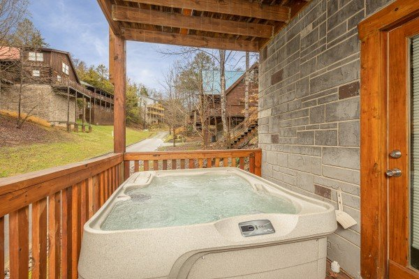 Hot tub on a covered deck at Alpine Tranquility, a 4 bedroom cabin rental located in Pigeon Forge