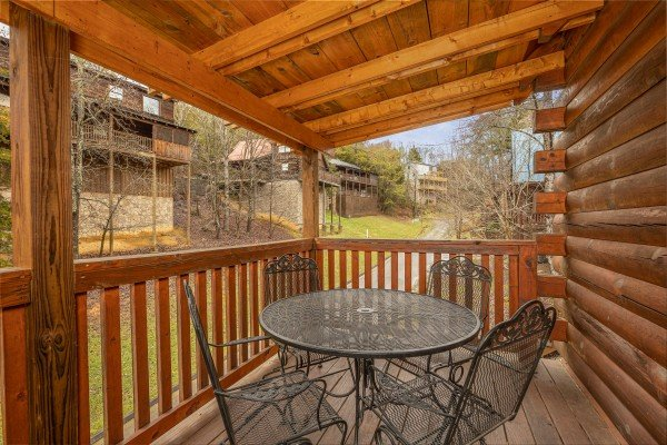Outdoor dining for four on a covered deck at Alpine Tranquility, a 4 bedroom cabin rental located in Pigeon Forge
