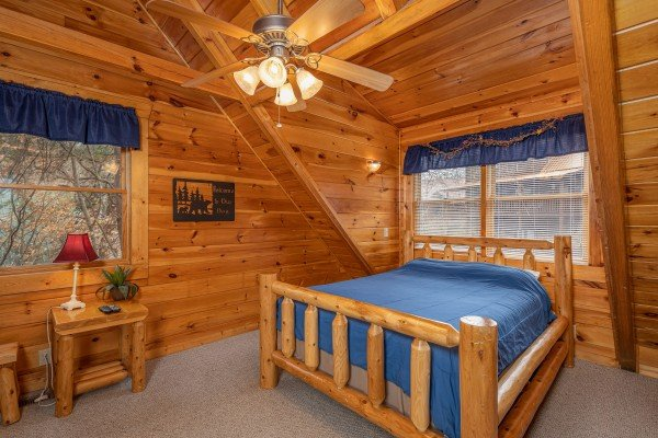 Bedroom with a queen log bed, table, and lamp at Alpine Tranquility, a 4 bedroom cabin rental located in Pigeon Forge