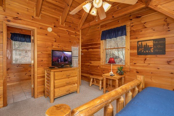 Dresser, TV, and en suite bath at Alpine Tranquility, a 4 bedroom cabin rental located in Pigeon Forge