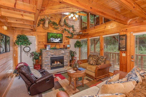Living room with fireplace and TV at Smokey Max Cabin, a 2 bedroom cabin rental located in Pigeon Forge