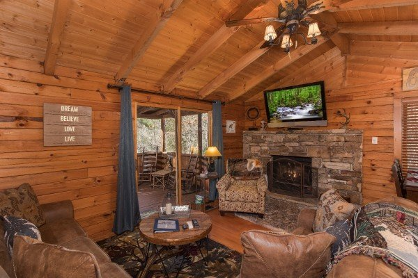 Living room with fireplace, TV, and deck access at Snuggle Inn, a 2 bedroom cabin rental located in Pigeon Forge