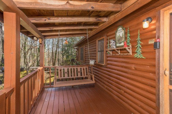 Swing on a covered deck at Snuggle Inn, a 2 bedroom cabin rental located in Pigeon Forge
