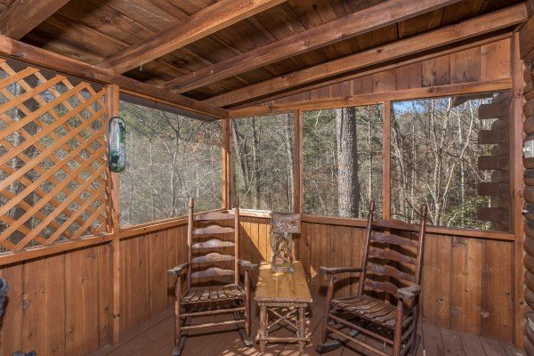 Rocking chairs on a screened in porch at Snuggle Inn, a 2 bedroom cabin rental located in Pigeon Forge