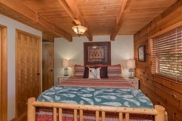 King size log bed at Snuggle Inn, a 2 bedroom cabin rental located in Pigeon Forge