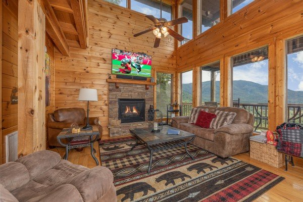Living room with fireplace, TV, and mountain views at 1 Awesome View, a 3 bedroom cabin rental located in Pigeon Forge