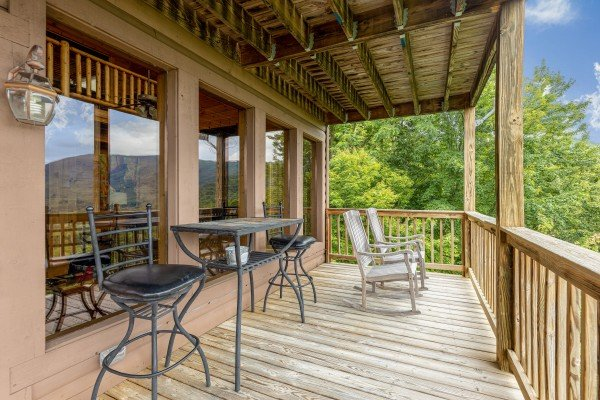 Deck with bistro set and rocking chairs at 1 Awesome View, a 3 bedroom cabin rental located in Pigeon Forge