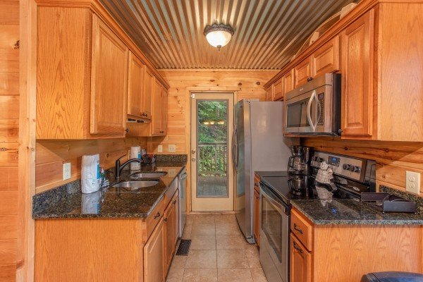 Galley kitchen with stainless appliances at License to Chill, a 3 bedroom cabin rental located in Gatlinburg