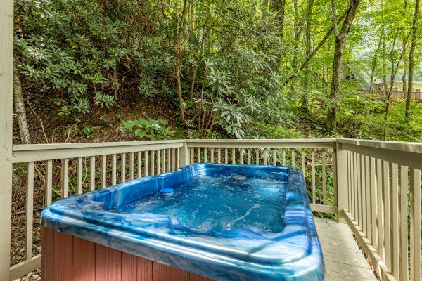 Hot tub on a deck surrounded by trees at License to Chill, a 3 bedroom cabin rental located in Gatlinburg
