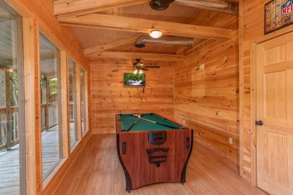 Pool table in a room with lots of natural light on the deck at License to Chill, a 3 bedroom cabin rental located in Gatlinburg