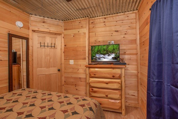 Bedroom with a chest of drawers and a TV at License to Chill, a 3 bedroom cabin rental located in Gatlinburg