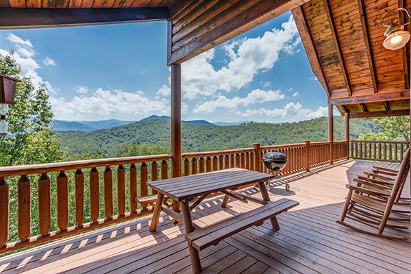 Picnic table, two rocking chairs, and a charcoal grill on a covered deck at Endless View, a 4-bedroom cabin rental located in Pigeon Forge