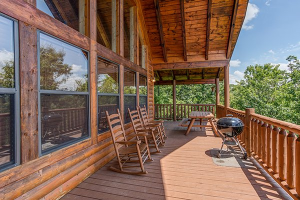 Deck rockers, a picnic table, and a charcoal grill on the covered deck at Endless View, a 4-bedroom cabin rental located in Pigeon Forge