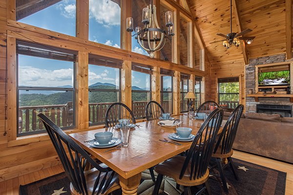 Dining space for six next to floor-to-ceiling windows at Endless View, a 4-bedroom cabin rental located in Pigeon Forge