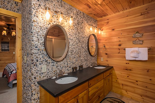 His and hers sinks with a river stone backsplash at Endless View, a 4-bedroom cabin rental located in Pigeon Forge