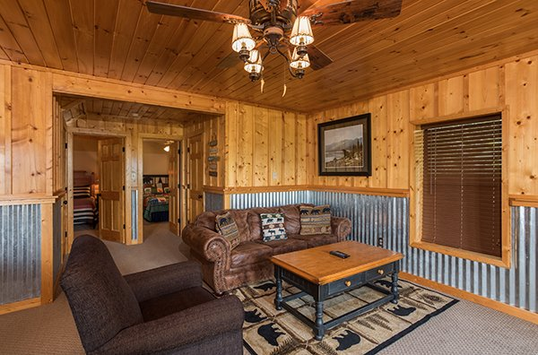 Sofa and chair adjacent to the game room on the lower level at Endless View, a 4-bedroom cabin rental located in Pigeon Forge