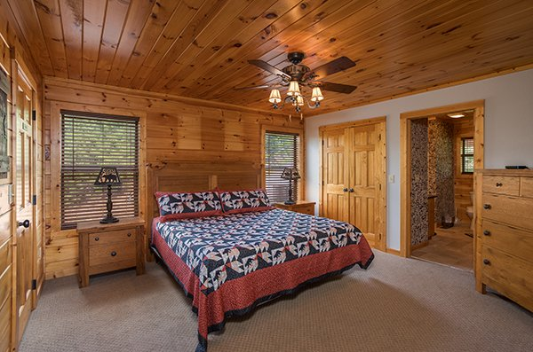 Bedroom with a king-sized bed, end tables, dresser, and en suite bath at Endless View, a 4-bedroom cabin rental located in Pigeon Forge