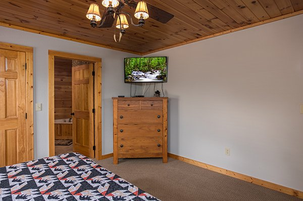 Television and dresser in the bedroom next to the en suite at Endless View, a 4-bedroom cabin rental located in Pigeon Forge