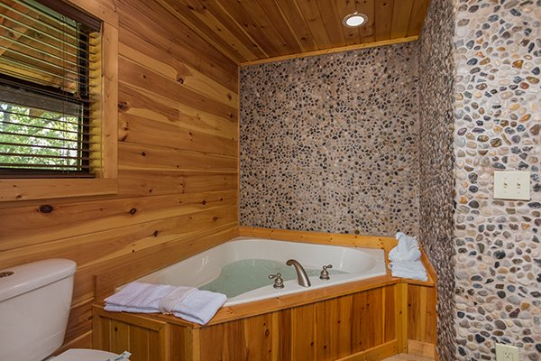 Corner jacuzzi with riverstone surround at Endless View, a 4-bedroom cabin rental located in Pigeon Forge