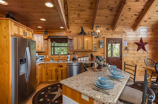 Kitchen with stainless appliances and breakfast bar seating at Endless View, a 4-bedroom cabin rental located in Pigeon Forge