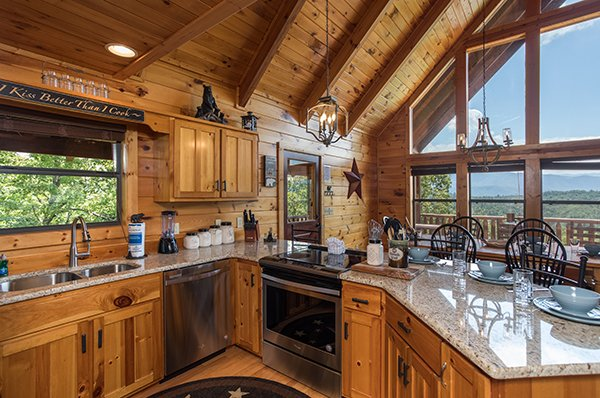 Looking out into the dining area and the views from the floor-to-ceiling windows at Endless View, a 4-bedroom cabin rental located in Pigeon Forge