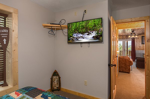 Bedroom off the game room with a wall-mounted TV at Endless View, a 4-bedroom cabin rental located in Pigeon Forge