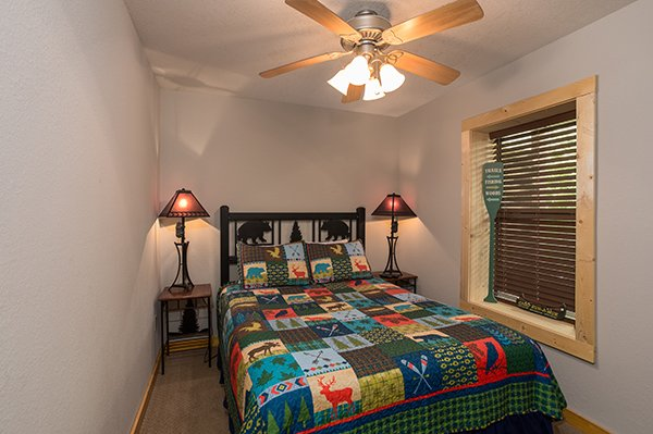 Basement bedroom with two end tables and a bear-themed bed at Endless View, a 4-bedroom cabin rental located in Pigeon Forge