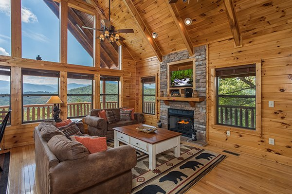 Living room with vaulted ceiling and floor-to-ceiling windows at Endless View, a 4-bedroom cabin rental located in Pigeon Forge