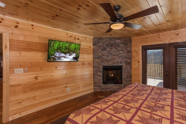 Fireplace and tv in the king bedroom with deck access at Gonzo's Outpost, a 3-bedroom cabin rental located in Pigeon Forge