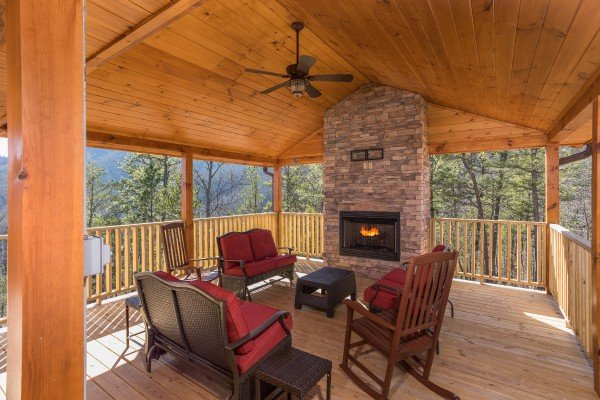 Seating area with an outdoor fireplace on a covered deck at Gonzo's Outpost, a 3-bedroom cabin rental located in Pigeon Forge