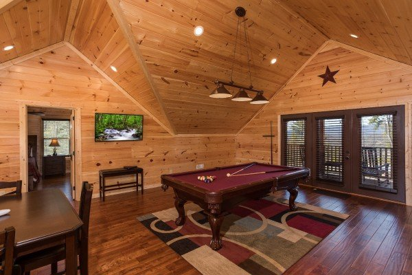 Pool table and TV in the loft space at Gonzo's Outpost, a 3-bedroom cabin rental located in Pigeon Forge