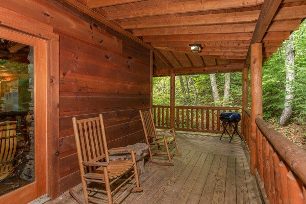 Rocking chairs and a charcoal grill on a covered deck at Fishing Bears, a 1-bedroom cabin rental located in Gatlinburg