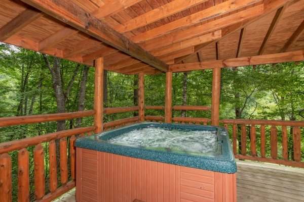 Hot tub on a covered deck with wooded views at Fishing Bears, a 1-bedroom cabin rental located in Gatlinburg