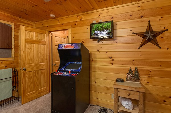 Arcade game and TV at Gentleman Jack's, a 3-bedroom cabin rental located in Gatlinburg
