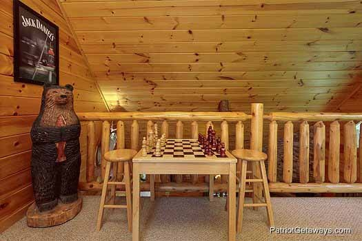 Checkers table next to wooden bear statue in the lofted game room of Gentleman Jack's, a 3-bedroom cabin rental located in Gatlinburg