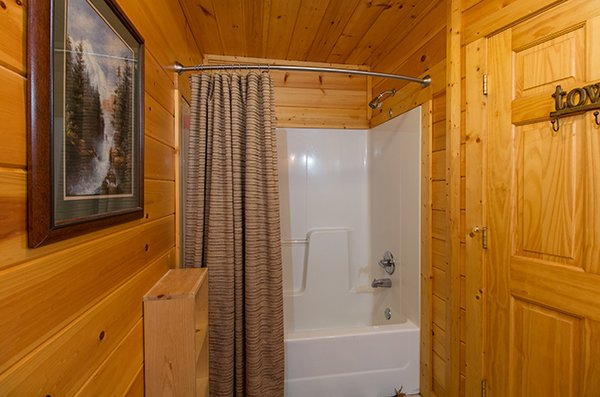 Bathroom with a tub and shower at Gentleman Jack's, a 3-bedroom cabin rental located in Gatlinburg