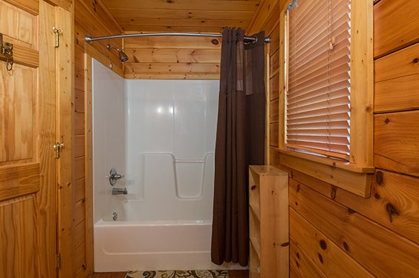 Bathroom with a tub and shower adjacent to the first bedroom at Gentleman Jack's, a 3-bedroom cabin rental located in Gatlinburg