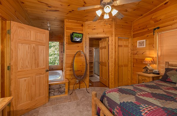 First bedroom with a jacuzzi tub, TV, mirror, and en suite bath at Gentleman Jack's, a 3-bedroom cabin rental located in Gatlinburg