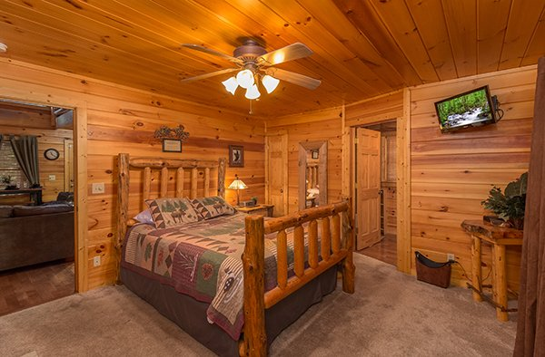 First bedroom with a log bed and television at Gentleman Jack's, a 3-bedroom cabin rental located in Gatlinburg