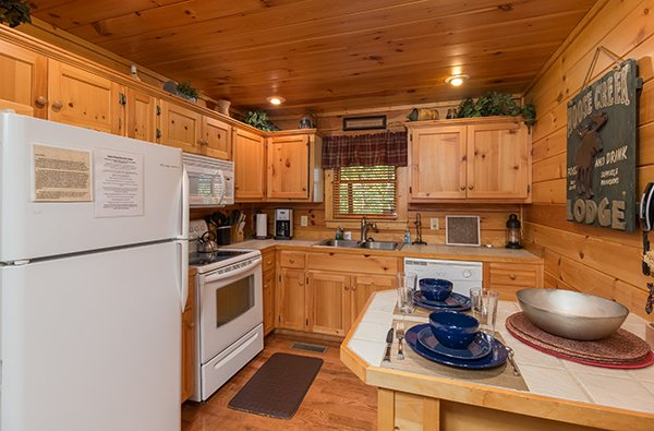 Kitchen with white appliances and dining space for two at Gentleman Jack's, a 3-bedroom cabin rental located in Gatlinburg