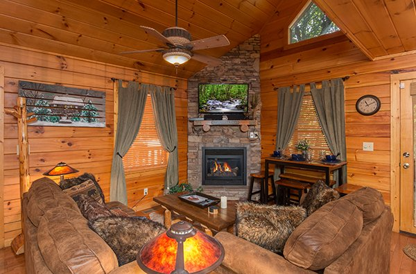 Living room with stone fireplace and television Gentleman Jack's, a 3-bedroom cabin rental located in Gatlinburg