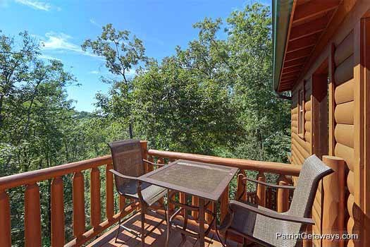 patio table and chairs on the deck of the third floor at gentleman jack's a 3 bedroom cabin rental located in gatlinburg