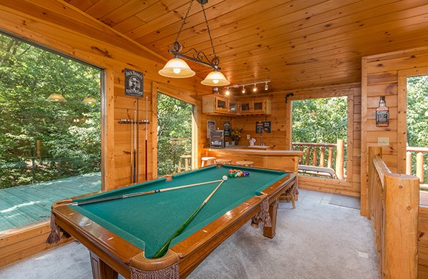 Pool table and a wet bar next to deck access at Gentleman Jack's, a 3-bedroom cabin rental located in Gatlinburg
