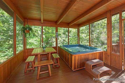 Hot tub and picnic table on screened deck at Gentleman Jack's, a 3-bedroom cabin rental located in Gatlinburg