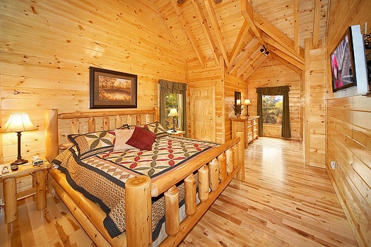 King-sized bed with flat screen tv in the second floor bedroom at Big Bear Falls, a 2-bedroom cabin rental located in Gatlinburg