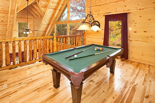 Green felt pool table and custom log banister in the lofted game room at Big Bear Falls, a 2-bedroom cabin rental located in Gatlinburg
