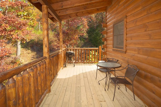 covered deck with table and chairs along with grill at big bear falls a 2 bedroom cabin rental located in gatlinburg
