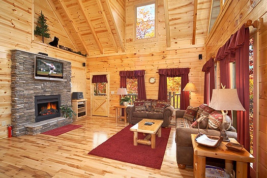 sofa bed facing a stone fireplace with tv mounted above mantle at big bear falls a 2 bedroom cabin rental located in gatlinburg